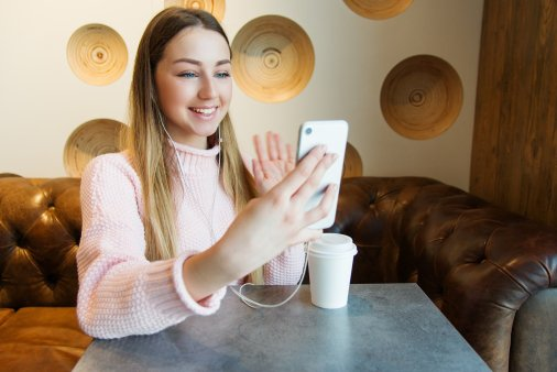 caucasian woman holding her white phone up smiling and waving at the screen.