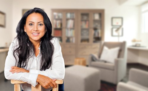 caucasian woman with white blouse smiling with a chair in the background