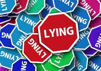 different colored signs that says lying on them