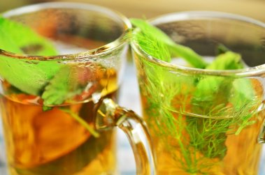 two glasses of tea with peppermint in them.