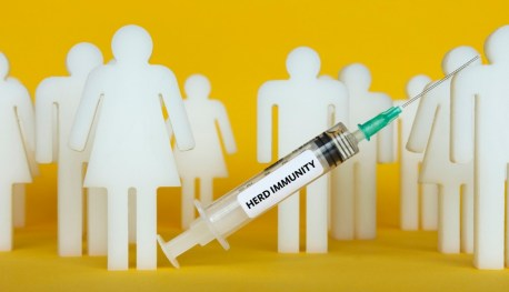 "white figures of people with a shot in front of them with the word ""herd immunity"" on the shot"