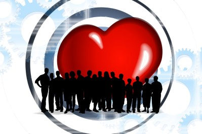 silhouette of a group of people standing in front of a large red heart.