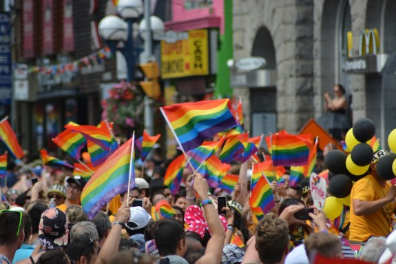 people in the street holding rainbow flags