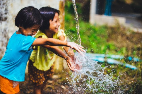 two young asian kids playing with water