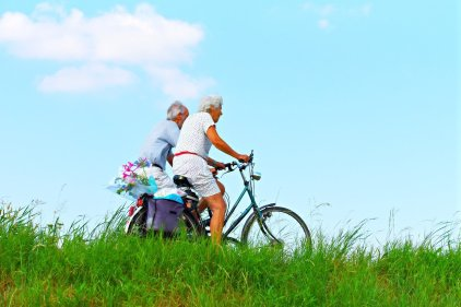 two older adults riding bicycles next to each othercyc