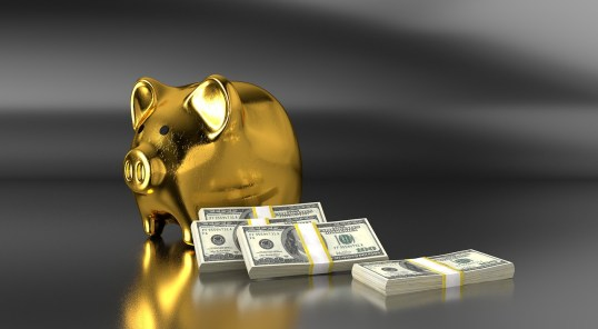 gold piggy bank with hundred dollar bills banded next to it