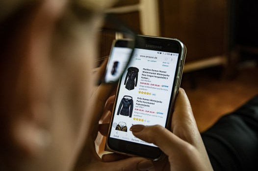 person looking at cellphone with coats and ratings on each