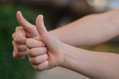 two caucasian hands with their thumbs up