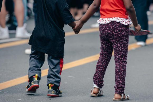 Children, also known as peds, holding hands walking down street.