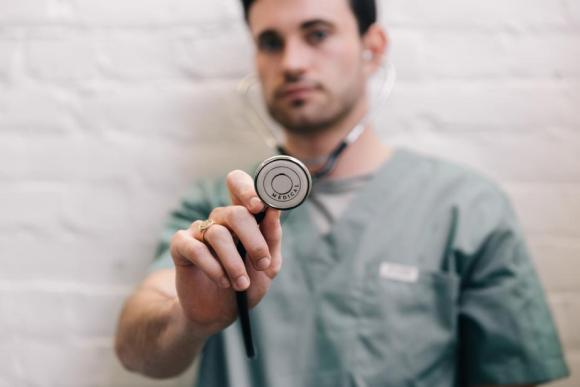A pediatrician, practioner of pediatrics also known as PEDS, holds a stethescope