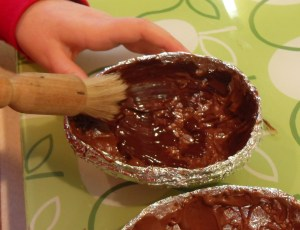 Painting chocolate onto egg mould.
