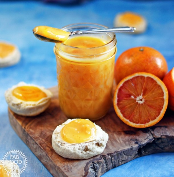 Granny's Quick Blood Orange Curd in a glass jar on wooden board with spoon and blood oranges with scones scattered around.