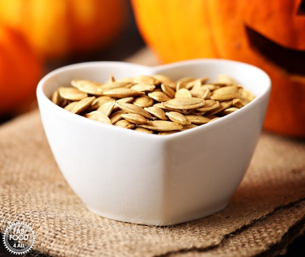 Close up or Roasted Pumpkin Seeds in a dish with Pumpkins & jack-o-lantern in the background.