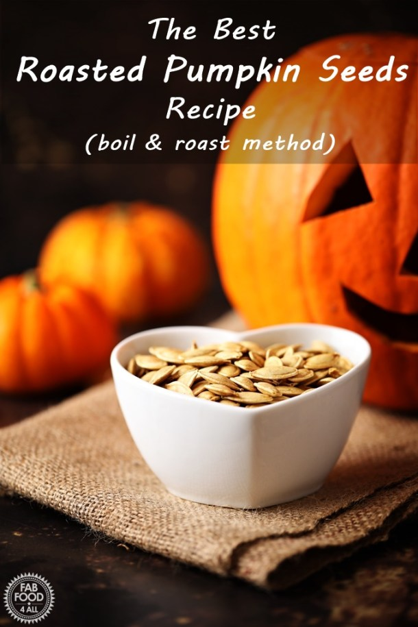 Roasted Pumpkin Seeds in a dish with Pumpkins & jack-o-lantern in the background. Pinterest image.