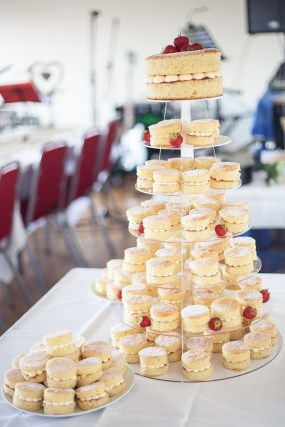 a tower of mini victoria sponge cakes with glitter covered strawberries