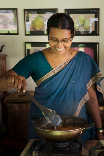 Administrator and chef's assistant Onamly, wearing a jewel toned blue sari with gold trim, smiles as she gently stirs food cooking simmering in a wok.