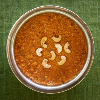 Bright orange carrot halwa in a round serving dish topped with halved cashew nuts. As prepared at The Bangala, Karaikudi.