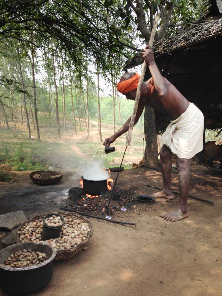 A shirtless South Indian man wearing an orange head wrap and a white dhoti carries a long wooden pole with a metal poker end. He leans forward against the pole as he pours a cup of water into his steaming pot, which sits on a ground level fire. One stone bowl and one basket of roasted cashews sit in the foreground.