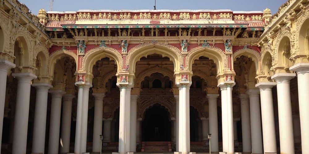 The massive white columns of Nayakar Mahal Palace tower above the central courtyard, where black folding chairs are set up for a performance.