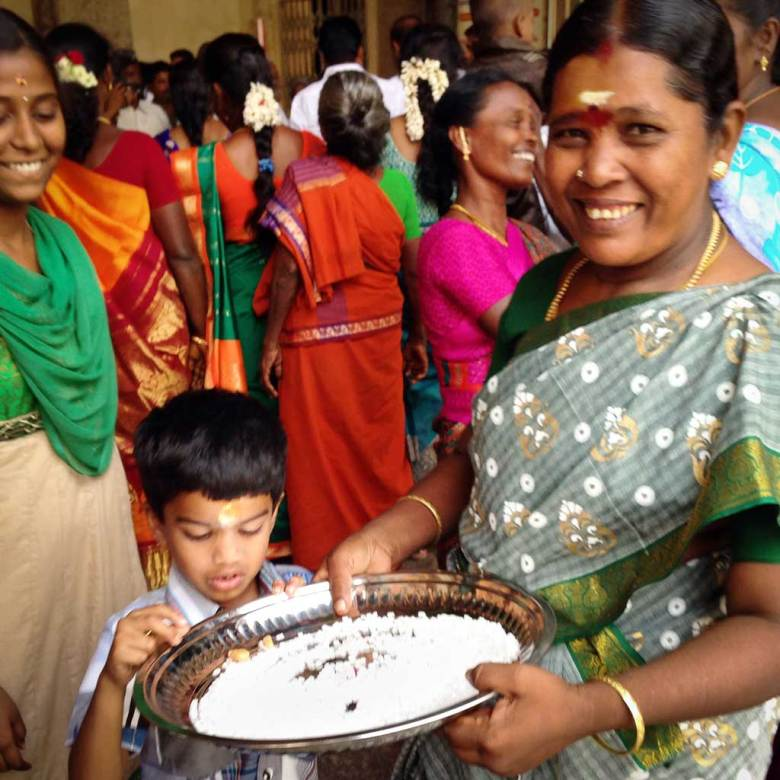 A woman wearing a green sari holds a tray of rock sugar treats as a young boy looks on and brightly-dressed women mingle in the background at the Meenakshi Amman Temple, Madurai.