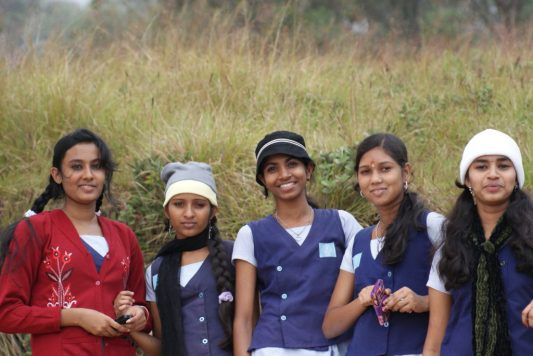 Five South Indian school girls dressed in purple uniforms pose and smile in front of a field of grass.