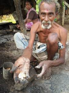 A shirtless, elderly South Indian man wearing a light coloured dhoti squats on the ground with his knees near his shoulders as he extends his hand out to the camera and offers a palm full of freshly roasted cashew nuts.