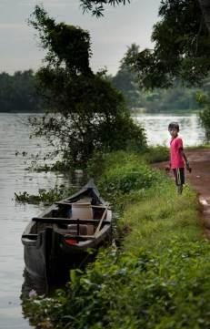 A boy waits by transport, a canoe along the Kerala Backwaters.