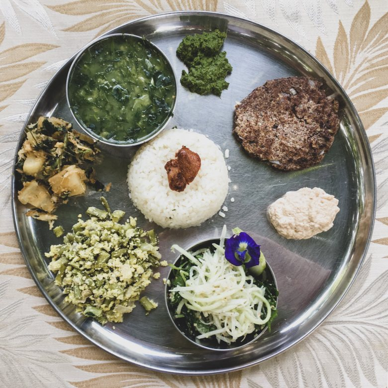 Small portions of colourful South Indian food sit in a circle on a white plate.