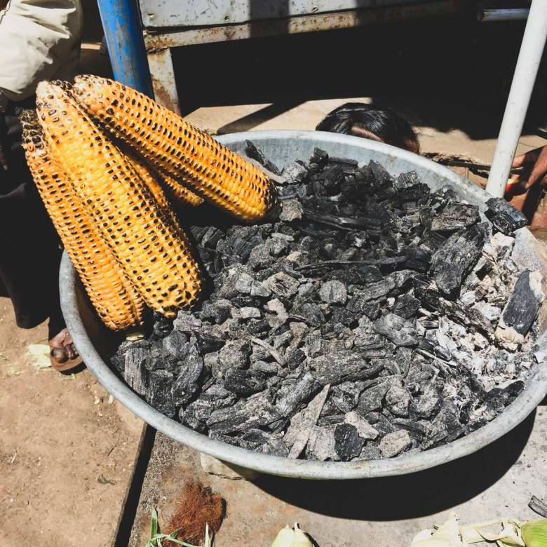 Grilled corn on charcoal.