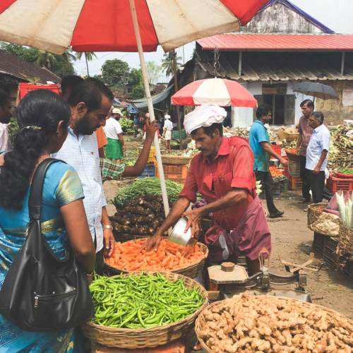 A man sells vegetables under a red and white umbrella at the Kalpaka vegetable market.