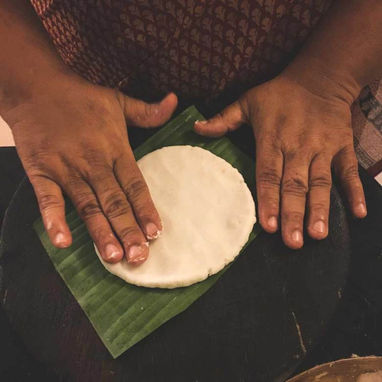 A hand pats flat Pathiri bread dough on a banana leaf.
