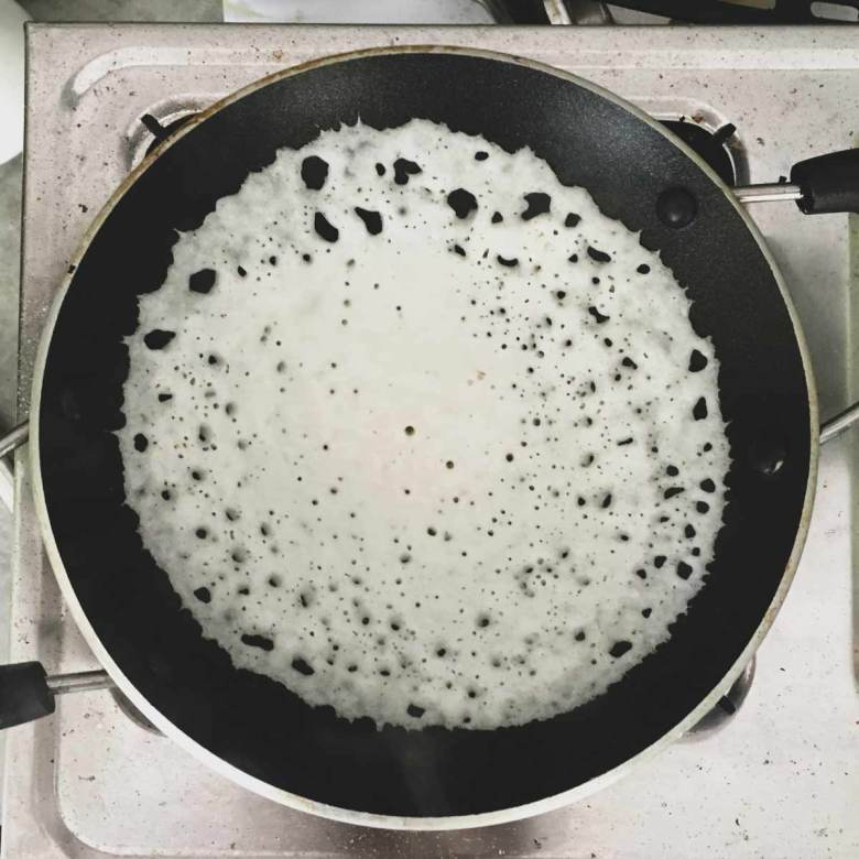 Appam cooking in a pan