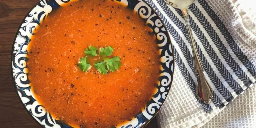 Bright red tomato soup with a green cilantro garnish.