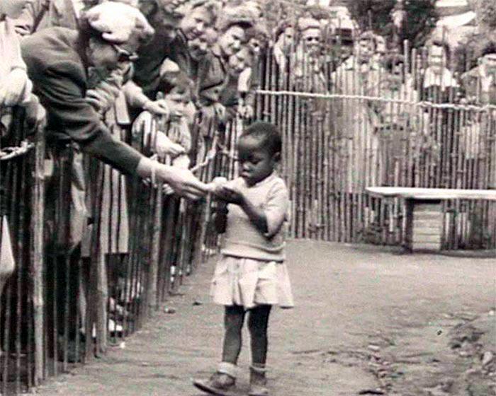 Посетитель в человеческом зоопарке угощает африканскую девочку бананом