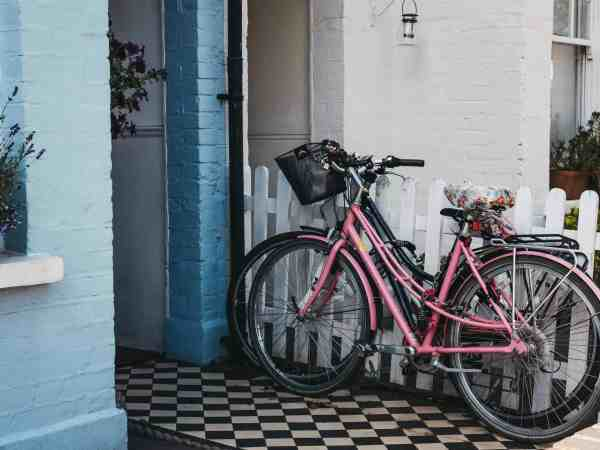 London, UK – August 1, 2018: His and hers bikes in front on a pastel blue house in Barnes, an affluent residential area of London famous for its village atmosphere.