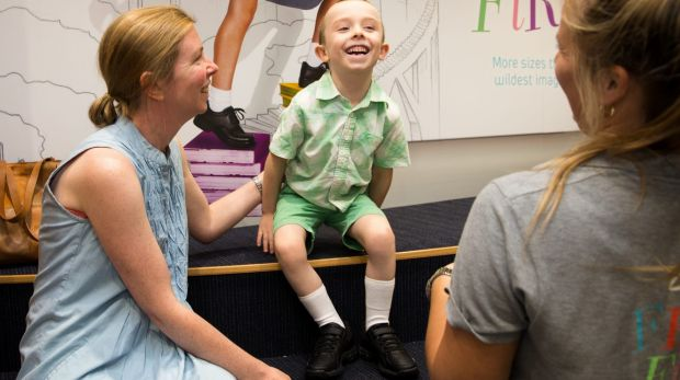 Herbie Khan with his mother, Nicole Graham, assisted by Paulina Jagiellowicz, tries on new school shoes.