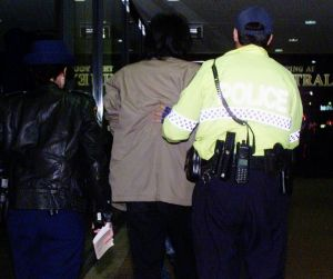 About 50 alleged gangsters, including this unidentified person, were arrested in this raid on a Chinese restaurant in 2002.