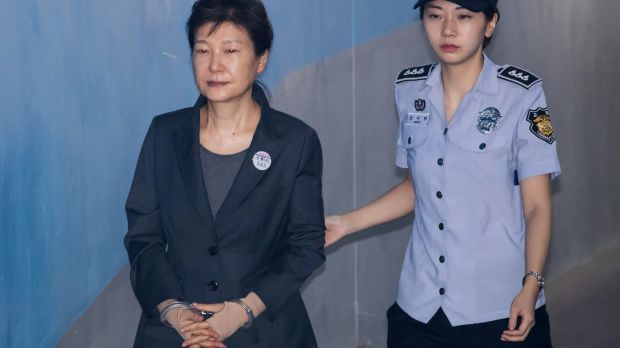 Park Geun-hye, former president of South Korea, is escorted by a prison officer as she arrives at court in June.