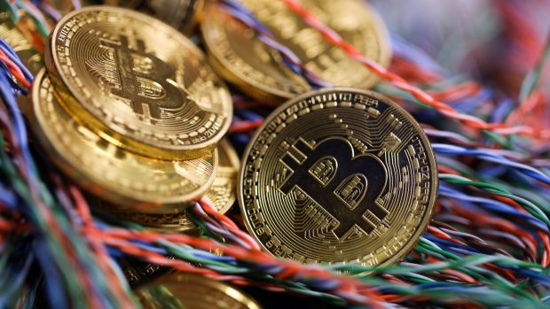 Bitcoins sit among twisted copper wiring inside a communications room at an office in this arranged photograph in ...