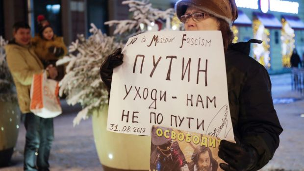 A protester stands in a one-person picket, holding a poster reading 'Putin go away-we do not follow your path!' in ...