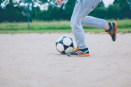 boy running with soccer ball in blog about soccer injuries, and how physical therapy can help