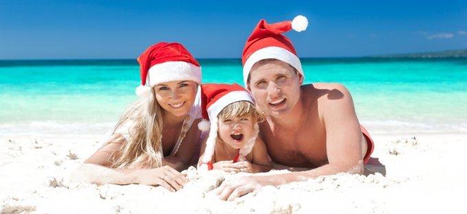 Happy family celebrating Christmas on beach