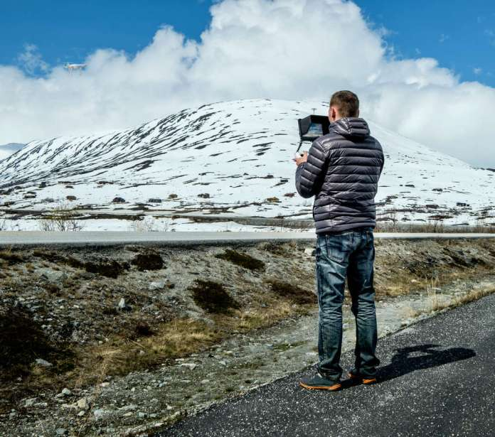 man with drone near mountain