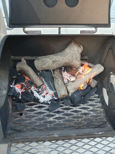 Smoker firebox with lit charcoal and peach wood just starting to catch light