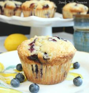 muffin on plate with fresh blueberries around it with a tray of muffins in the background