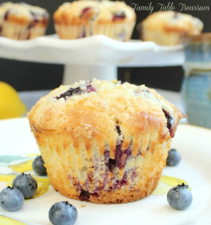 blueberry muffin on a plate with the wrapper removed, a tray of blueberry muffins in the background, a cup of coffee and lemon