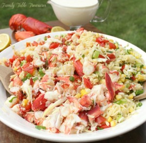 lobster orzo salad in a bowl with dressing and lobster shell in the background