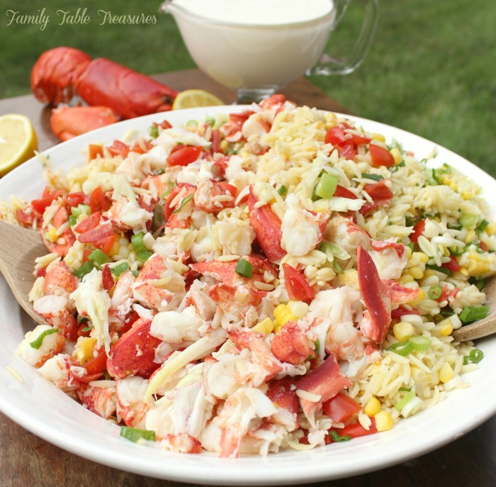 Lobster Orzo Salad in a serving bowl with dressing in the background