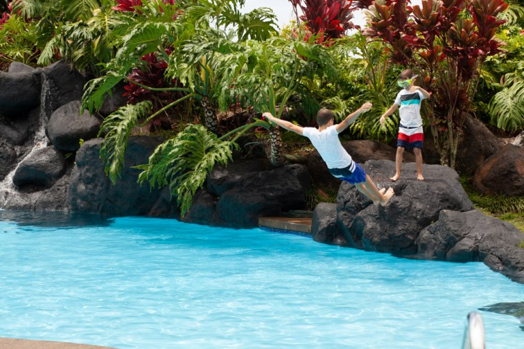 Photo of boy falling backward into pool of water, boy wearing goggles stands on rock looking on