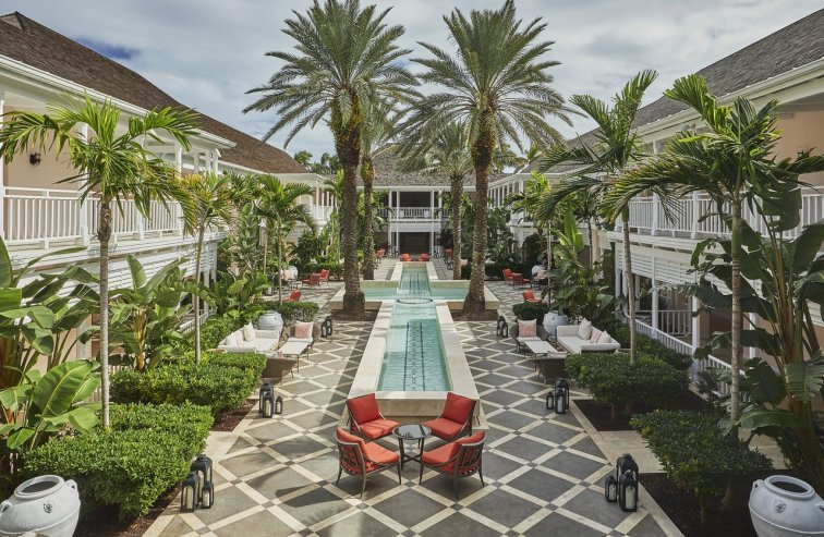 Outside view of Ocean Club, with cross shaped pool, surrounded by palm trees, 4 orange chairs